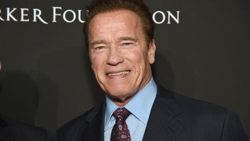 Arnold Schwarzenegger, la costum, zâmbește către camera foto