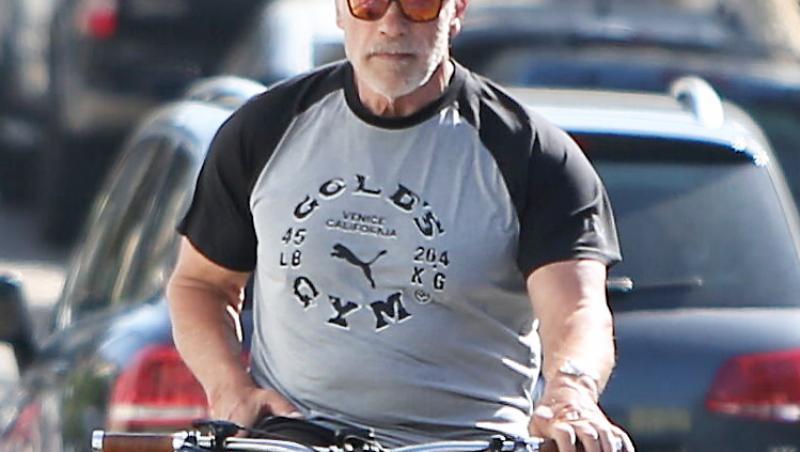 Schwarzenegger purta o șapcă și ochelari de soare, pantaloni scurți și un tricou cu inscripția numelui unei săli de forță