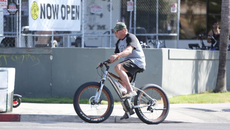 Schwarzenegger, pe bicicletă, purta o șapcă și ochelari de soare, pantaloni scurți și un tricou cu inscripția numelui unei săli de forță