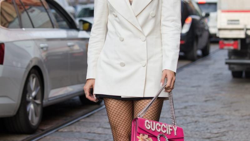 alina ceusan intr-o rochie alba, ochelari de soare, geanta roz pe strada
