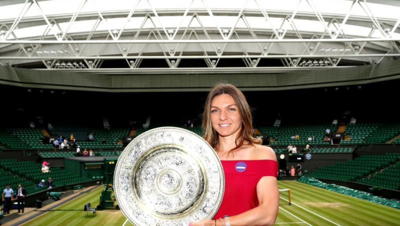 Simona Halep, cu trofeul de la Wimbledon, în 2019, purtând o rochie roșie