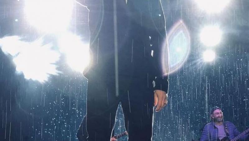 laurentiu duta imbracat in negru candtand pe scena, in ploaie