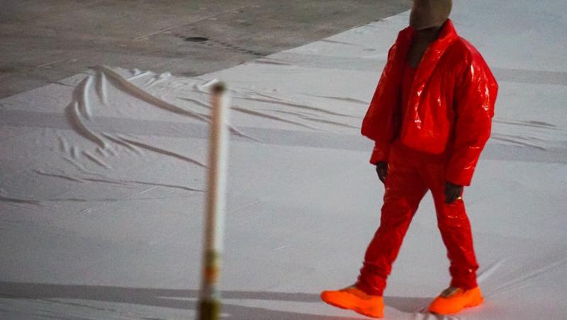 kanye west imbracat in rosu in mijlocul stadionului unde a avut loc evenimentul de lansare al celui de-al 10-lea album