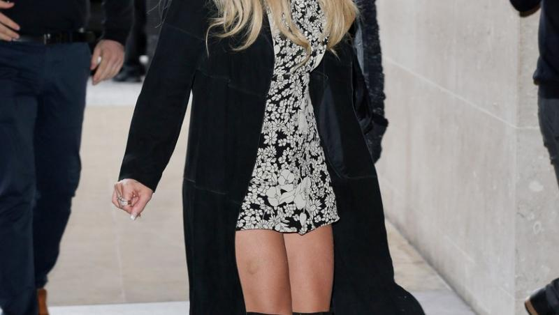 britney spears pe strada, intr-o rochie scurta alba, cu cizme negre, palton negru, palarie neagra si ochelari negri de soare