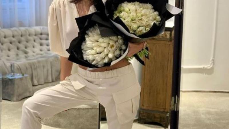 dana budeanu intr-un trening alb cu un buchet de flori albe in mana