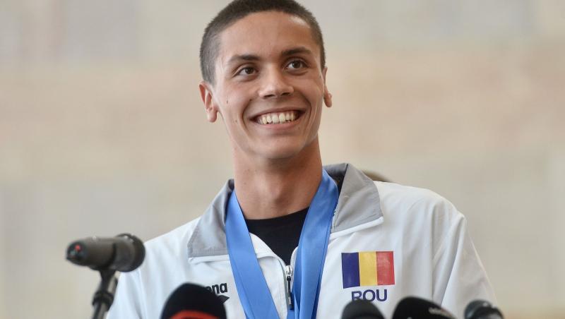 David Popovici vorbește la microfon și zâmbește
