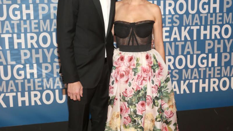 Mila Kunis și Ashton Kutcher, îmbrăcați elegant. El, în costum, ea, într-o rochie cu imprimeu