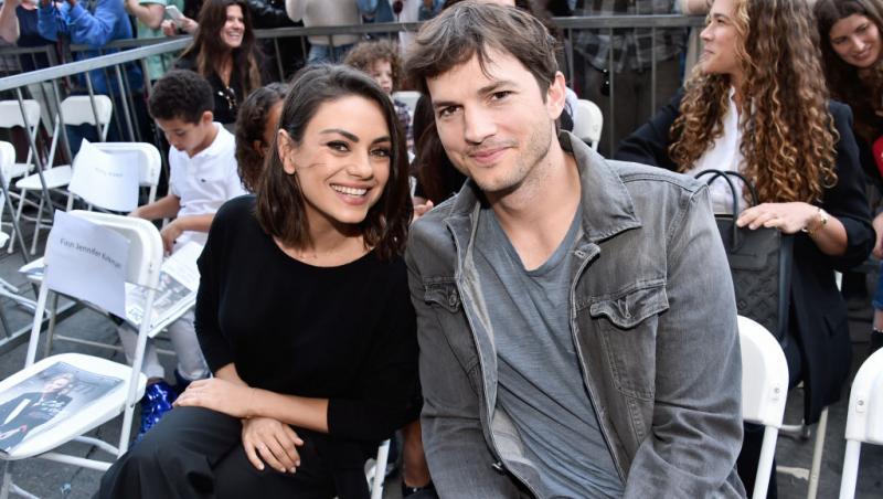 Mila Kunis și Ashton Kutcher așezați pe niște scaune albe, îmbrăcați casual
