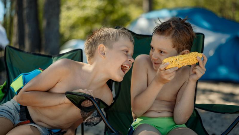 doi copii care stau pe sezlong si mananca dintr-un porumb fiert