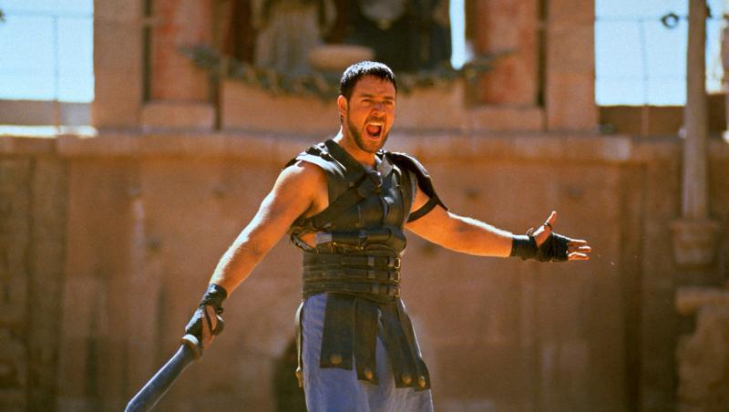 russell crowe în filmul gladiatorul, țipând la public, în arena gladiatorilor. are sabia în mână și e îmbrăcat în armură, cu fundal bej în spate