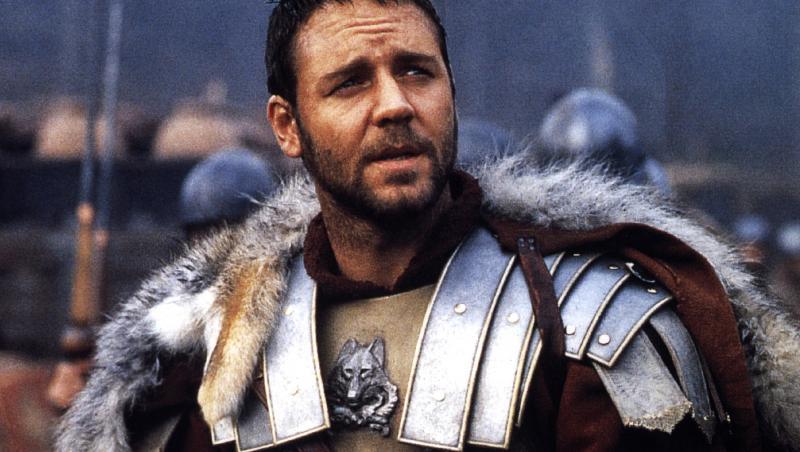 russell crowe în filmul gladiatorul, pe terenul de luptă, îmbrăcat în armura de general roman, cu armură arginie și pelerină roșie cu blană