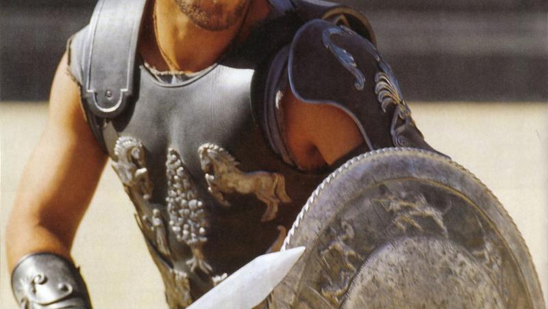 russell crowe în filmul gladiatorul, în arena gladiatorilor. are sabia în mână și e îmbrăcat în armură, se apără cu scutul, cu fundal bej în spate