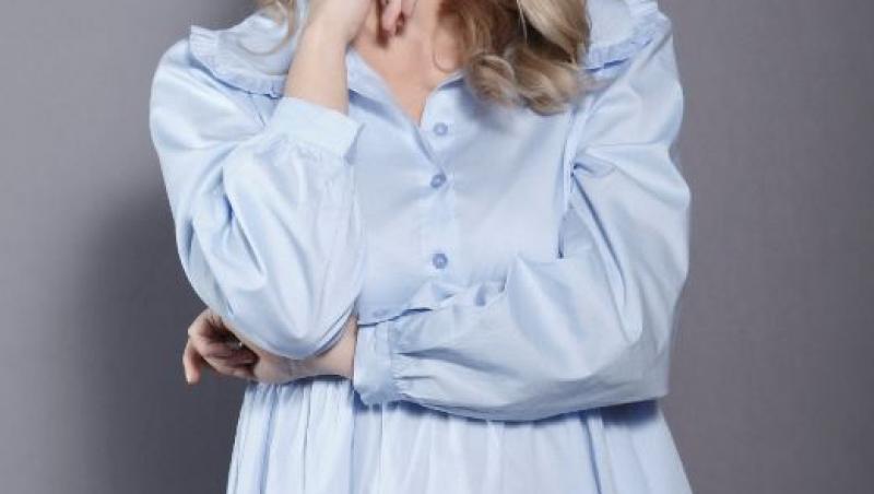 Ilona Brezoianu, îmbrăcată într-o rochie bleu, gânditoare