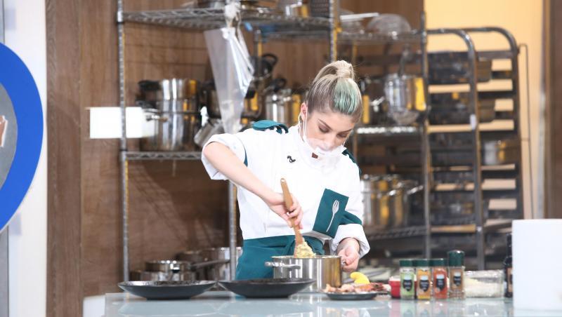 Elena Matei în tunică albă și verde, gătește