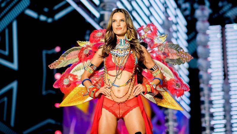 alessandra ambrosio pe podiumul de modă victorias secret, fundal albastru cu negru în spate. ea poartă un costum colorat, cu lenjerie de culoare roșie, aripi cu roșu, galben și albastru, colier mare la gât
