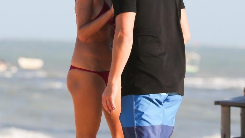 alessandra ambrosio și richard lee, la plajă în Brazilia, vara 2021. ea poartă un bikini roșu, el poartă un tricou negru și pantaloni scurți cu albastru și albastru închis. Fundal cu ocean și nisip