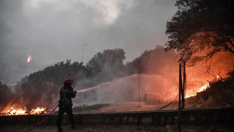 Pompier stingând flăcările din Grecia