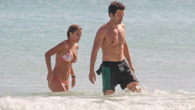 sebastian stan și alejandra onieva la plajă. fundal cu mare, ei ies din valuri. ea poartă un bikini cu alb și portocaliu, el poartă un costum de baie cu negru și verde