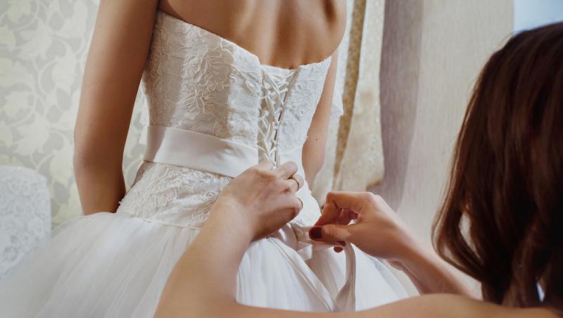 o mireasa ajutata sa se imbrace de catre domnisoara de onoare
