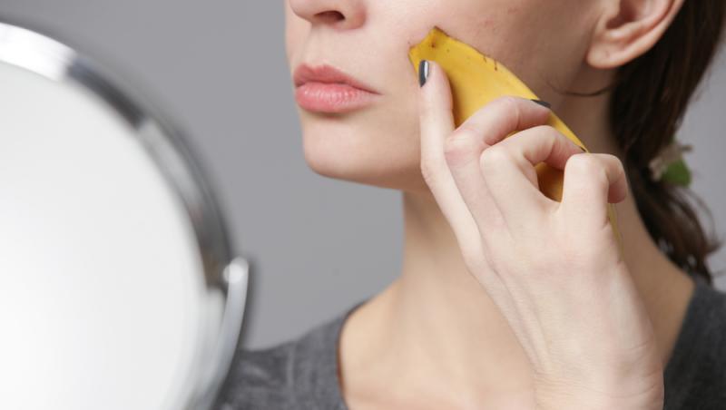 imagine cu o femeie care se da pe chip cu coji de banana