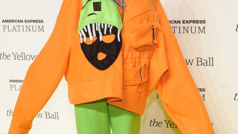 billie eilish intr-o camasa portocalie cu maneca lunga, pantaloni verzi si tenesi verzi