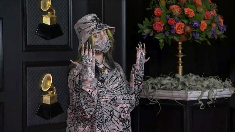 billie eilish intr-o camasa cu un imprimeu cu mov cu maneca lunga, masca de protectie, si palarie