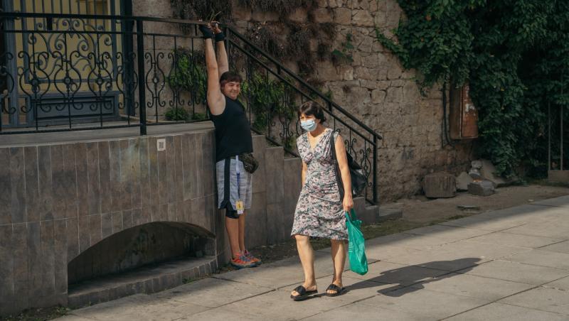 Cameraman în Asia Express, sezonul 4, lângă o femeie care poartă mască