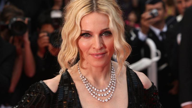madonna, pe covorul roșu, la premiera I Am Because We Are', la Cannes Film festival, în 2008. Îmbrăcată într-o rochie neagră, cu decolteu, lanț de diamante