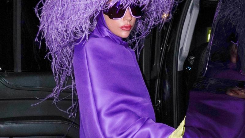 lady gaga intr-o rochie mov scurta cu o palarie mov pe cap si o pereche de ochelari de soare