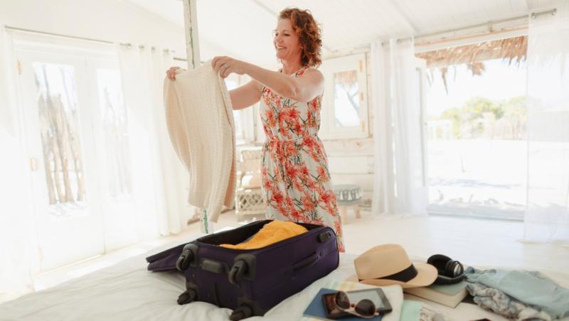 femeie care impacheteaza bagajul pe pat si pune haine in valiza pentru vacanta