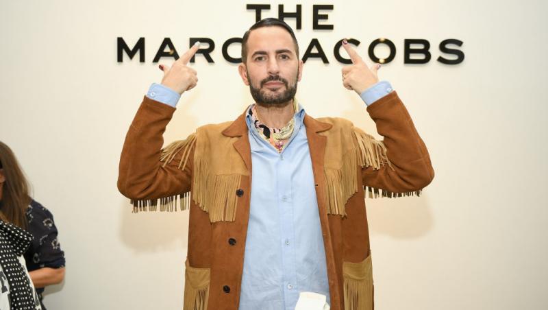 Marc Jacobs, îmbrăcat cowboy, cu o cămașă bleu. Ține mâinile în sus