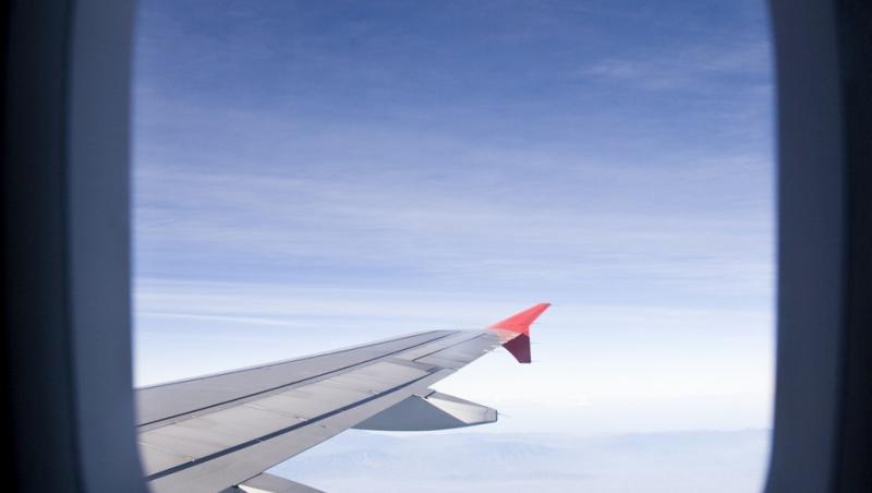 fereastra rotunda din avion prin care se vede cerul si o parte din avion