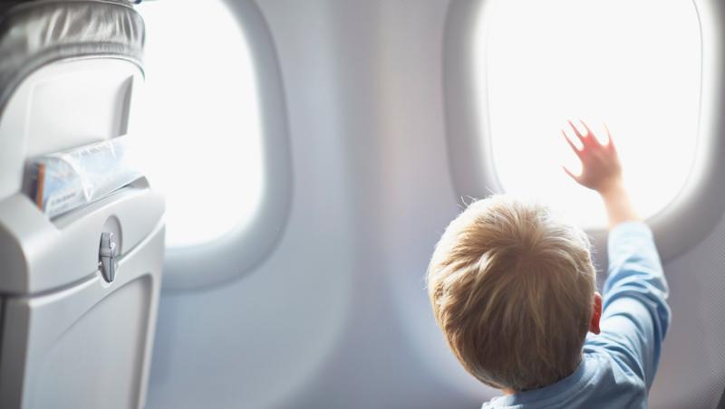 un baietel la una dintre ferestrele rotunde ale unui avion, stand cu spatele si cu o mana pe geam