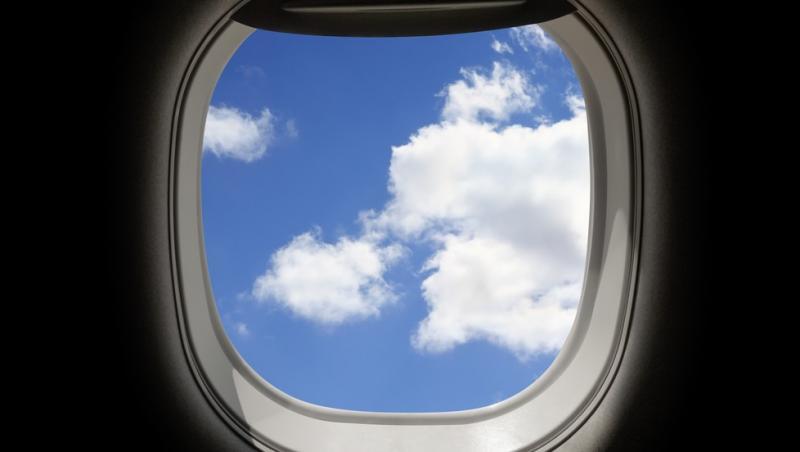 fereastra rotunda din avion prin care se vede cerul