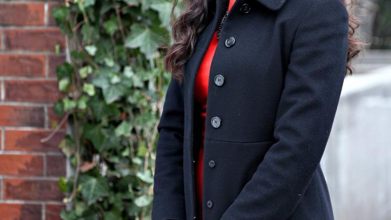 madalina bellariu intr-un palton negru si rochie rosie