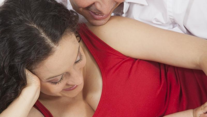 barbat in camasa alba si o femeie in rosu care se uita la un bebelus