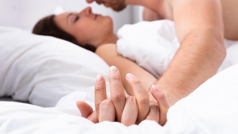 cuplu in patul acoperit cu o lenjerie alba
