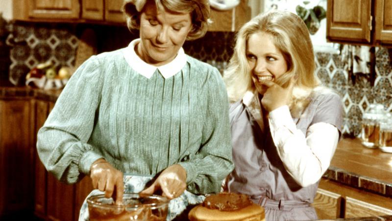 lucy ewing, în serialul dallas, în bucătărie cu bunica ei. îmbrăcată într-o bluză albă, cu vestă gri, părul blond lung
