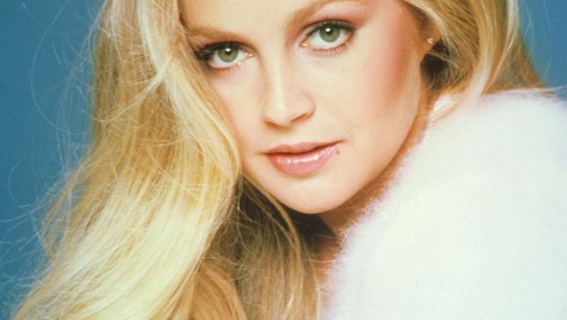 lucy ewing, beauty shot, cu părul blond lung, bluză albă pufoasă
