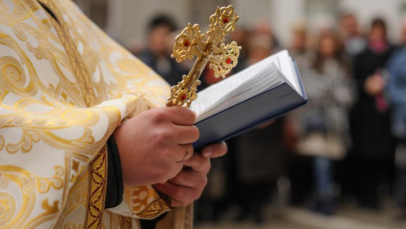 preot in biserica tine o cruce si citeste ceva din cartea sfanta