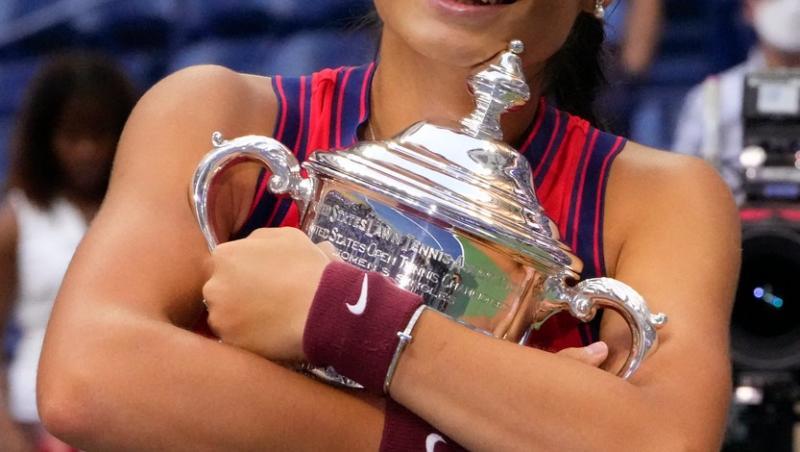 Emma Răducanu zâmbește și ține trofeul în brațe