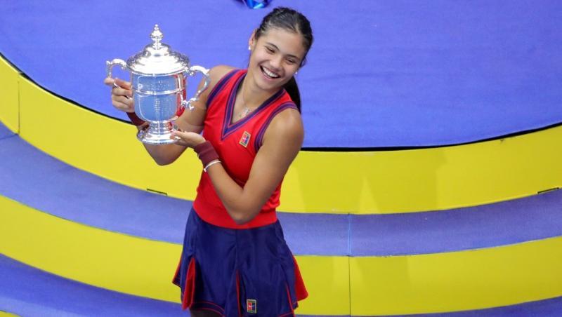 Emma Răducanu în echipament roșu-albastru, cu trofeul în mână