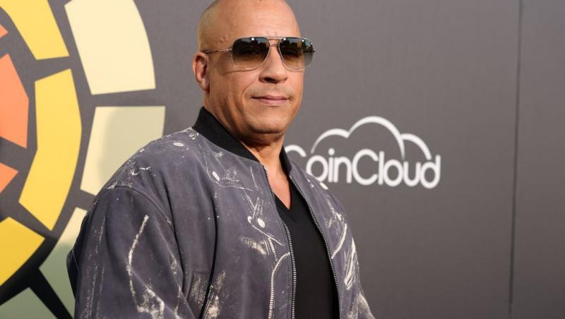 Vin Diesel, imbracat intr-o geaca din blugi, cu ochelari de soare la ochi
