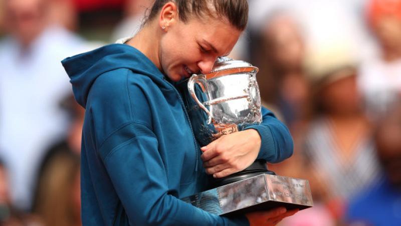 Simona Halep îmbrățișează trofeul pe terenul de tenis