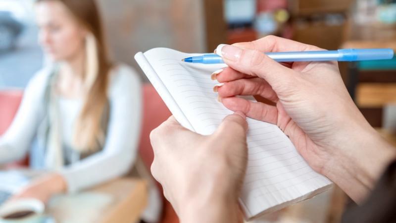 imagine cu o chelneriță in timp ce scrie un bilet