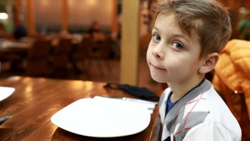 un băiețel luand masa