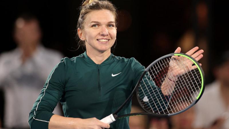 simona halep tine o racheta de tenis in mana si zambeste