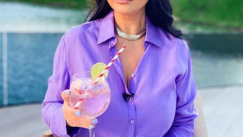 Gabriela Cristea într-o cămașă mov, cu un pahar în mână