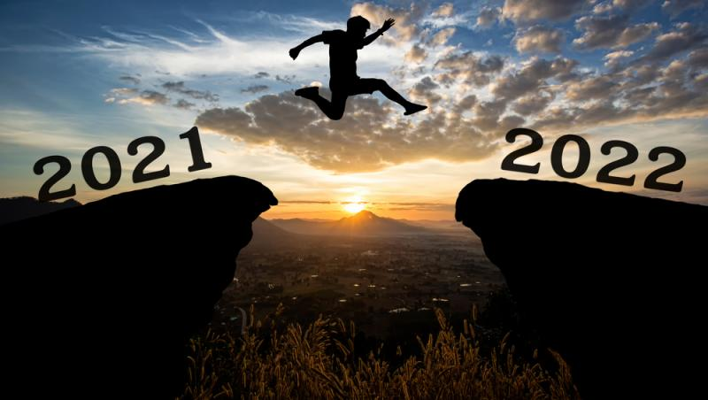 imagine cu un om sarind de pe o stanca pe alta, reprezentand anul 2021 si anul 2022