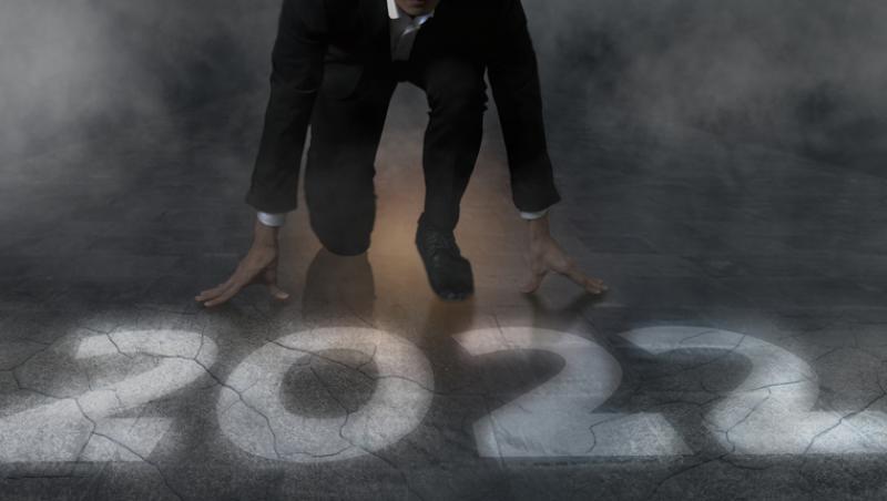 imagine cu anul 2022 scris langa un om imbracat la costum